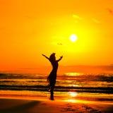 Silhouette de jeune femme sur la plage dans le coucher du soleil d'été Images libres de droits