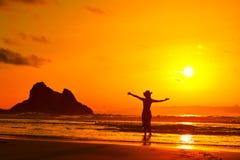 Silhouette de jeune femme sur la plage dans le lght de coucher du soleil d'été Images stock