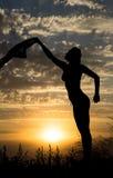 Silhouette de jeune fille avec le châle sur le fond du beau ciel bleu nuageux avec le coucher du soleil d'or jaune Image stock