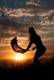 Silhouette de jeune fille avec le châle sur le fond du beau ciel nuageux avec le coucher du soleil orange Image libre de droits