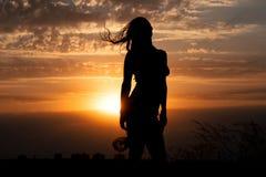 Silhouette de jeune fille avec le châle sur le fond du beau ciel nuageux avec le coucher du soleil rouge d'or Photos stock