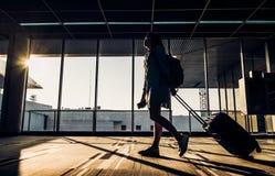 Silhouette de jeune fille marchant avec le bagage marchant à l'aéroport Photo libre de droits
