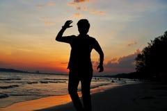 Silhouette de jeune homme sautant à la plage ayant le coucher du soleil dans des vacances d'été photos stock