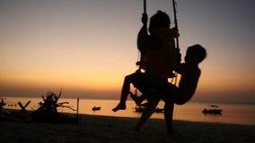 Silhouette de jeune mère balançant de petits enfants dans l'oscillation de plage à la plage de coucher du soleil Mouvement lent 1 banque de vidéos