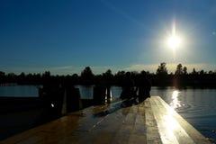 Silhouette de jeunes couples appréciant le coucher du soleil se reposant sur la plage Image libre de droits