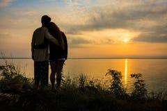Silhouette de jeunes couples asiatiques romantiques embrassant sur la banque du lac Photographie stock