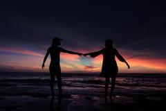 Silhouette de jeunes couples dans l'amour sur la plage quand coucher du soleil Photo stock