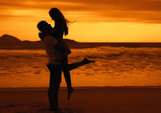 Silhouette de jeunes couples heureux d'amour étreignant à la plage sur le sunsetSilhouette de jeunes couples heureux d'amour étre Images libres de droits