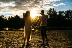 Silhouette de jeunes couples heureux dans l'amour regardant le ciel de coucher du soleil Images stock