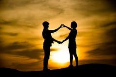 Silhouette de jeunes couples heureux dehors Image stock