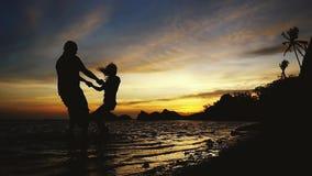 Silhouette de jeunes couples heureux tournant tenir autour des mains au coucher du soleil ?tonnant, mouvement lent 1920x1080 banque de vidéos