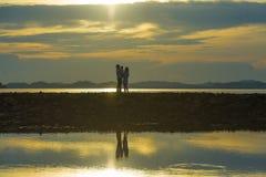 Silhouette de jeunes couples romantiques se tenant et jouant avec le petit bébé de fils ou de fille appréciant le coucher du sole images stock