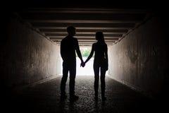 Silhouette de jeunes couples tenant des mains Image stock