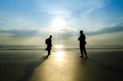 Silhouette de jeunes photographes sur la plage Photographie stock