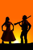 Silhouette de jupe et de cowboy de prise de femme avec l'arme à feu dans le lever de soleil Photographie stock libre de droits