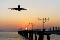 Silhouette de l'atterrissage d'avion dans le coucher du soleil Image stock