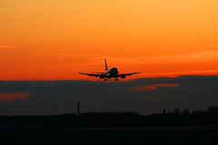Silhouette de l'avion d'atterrissage sur un coucher du soleil. Photo stock
