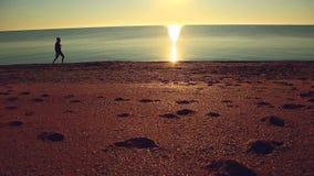Silhouette de l'homme actif de sport courant et s'exerçant sur la plage au coucher du soleil banque de vidéos