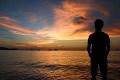 Silhouette de l'homme au coucher du soleil sur la plage images libres de droits