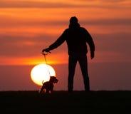 Silhouette de l'homme avec le chien au coucher du soleil Photos stock