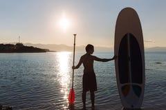 Silhouette de l'homme avec le ressac et la palette de petite gorgée dans des mains à l'océan Mode de vie de concept, sport Photos libres de droits
