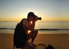 Silhouette de l'homme avec le sac à dos - photographe prenant la photo sur la caméra pendant le coucher du soleil photographie stock