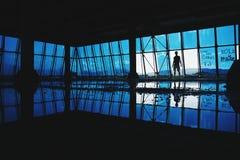 Silhouette de l'homme dans un bâtiment abandonné urbain avec les fenêtres bleues Image stock