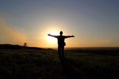 Silhouette de l'homme dans un domaine au coucher du soleil Photos libres de droits