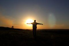 Silhouette de l'homme dans un domaine au coucher du soleil Photographie stock libre de droits