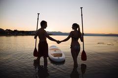 Silhouette de l'homme, de femme avec le ressac de petite gorgée et de palette à l'océan Mode de vie de concept, sport, amour Photo stock