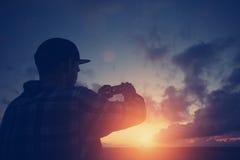Silhouette de l'homme prenant la photo du coucher du soleil avec le téléphone portable Photos stock