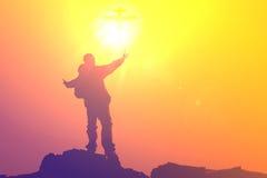 Silhouette de l'homme priant à la montagne supérieure avec la puissance abstraite d'un dieu de rayon de croix du soleil Photos stock