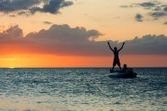 Silhouette de l'homme se tenant dans un bateau sur le fond du coucher du soleil Photos stock
