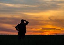 Silhouette de l'homme se tenant dans un domaine Images stock