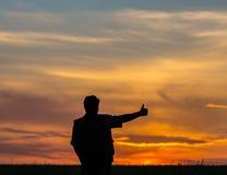 Silhouette de l'homme se tenant dans un domaine Photos stock