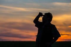 Silhouette de l'homme se tenant dans un domaine Photographie stock libre de droits