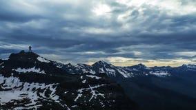 Silhouette de l'homme se tenant sur le concept surmonté par sommet à distance de haute montagne photographie stock libre de droits