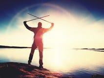 Silhouette de l'homme se tenant sur une roche et regardant vers le soleil de soirée Photo libre de droits