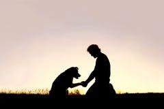 Silhouette de l'homme serrant la main à son Loyal Pet Dog Image stock