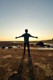 Silhouette de l'homme soulevant ses mains ou bras ouverts Photos libres de droits