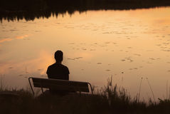 Silhouette de l'homme sur le banc dans le coucher du soleil d'or par le lac photographie stock libre de droits