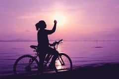 Silhouette de la célébration femelle heureuse avec le bras vers le s Photos stock