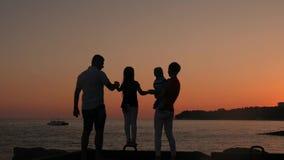Silhouette de la famille active ayant l'amusement et appréciant l'unité sur la plage au coucher du soleil banque de vidéos