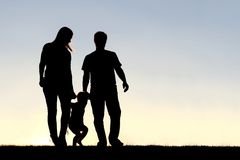 Silhouette de la famille de trois personnes marchant au coucher du soleil Images libres de droits
