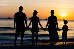 Silhouette de la famille heureuse ayant l'amusement sur la plage au temps de coucher du soleil Photos stock