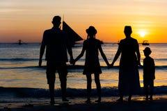Silhouette de la famille heureuse ayant l'amusement sur la plage au temps de coucher du soleil Photos libres de droits