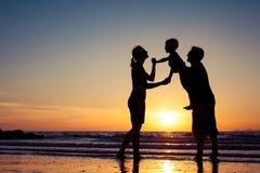 Silhouette de la famille heureuse qui jouant sur la plage au sunse Image libre de droits