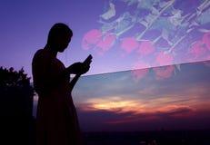 Silhouette de la femme à l'aide du smartphone au coucher du soleil sur le dessus de toit Photos stock