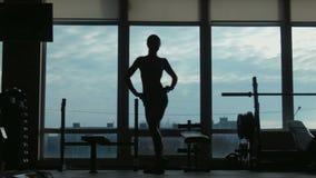 Silhouette de la femme attirante posant près d'une fenêtre dans le hall de forme physique banque de vidéos