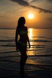 Silhouette de la femme dans le bikini marchant sur la plage au coucher du soleil Photos libres de droits